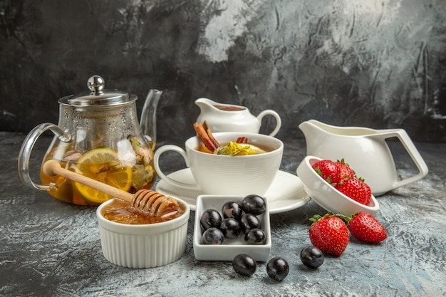 Vista frontal taza de té con aceitunas y miel en la superficie oscura desayuno de comida de la mañana