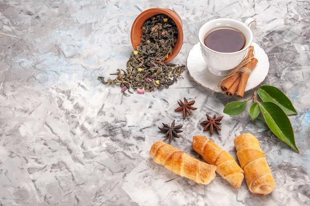 Vista frontal de la taza de té con bagels en la mesa blanca pastelería pastel de té
