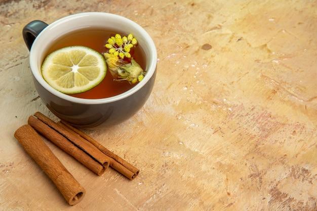 Vista frontal de una taza de té con canela y limón en la mesa de luz