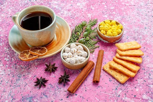Vista frontal de la taza de té con caramelos de canela y galletas en el escritorio rosa