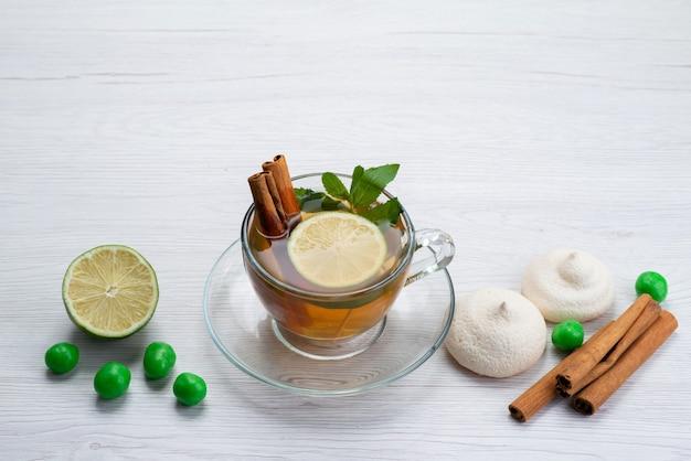 Vista frontal de una taza de té con caramelos de limón y galletas en blanco, dulces de postre de té