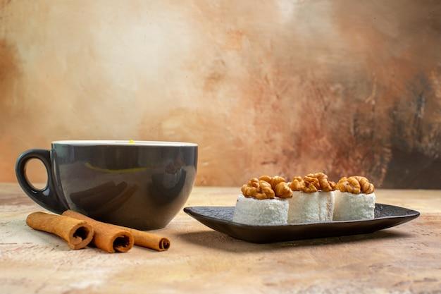 Vista frontal de una taza de té con confituras de nueces en la mesa de luz