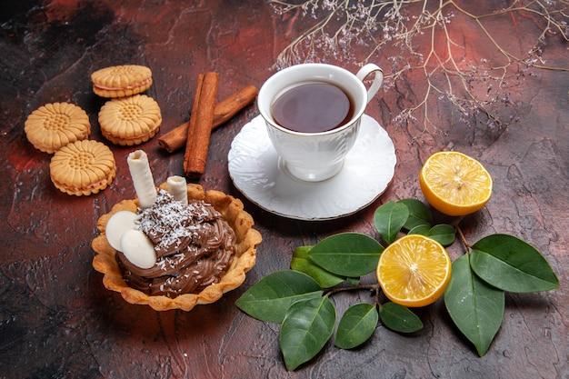 Vista frontal de una taza de té con un delicioso pastelito sobre fondo oscuro