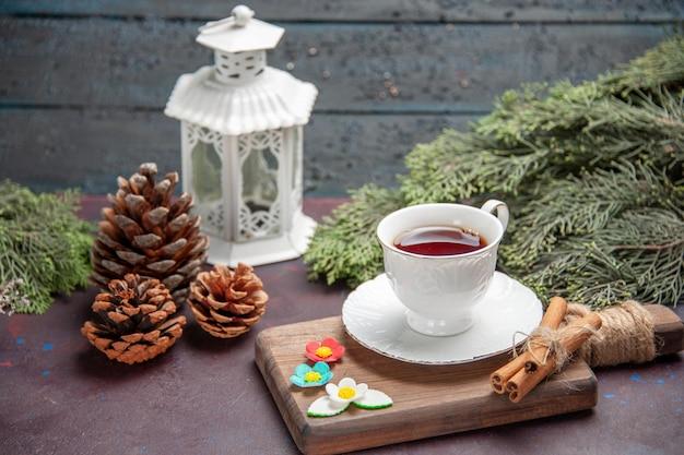 Vista frontal de la taza de té dentro de la taza de vidrio en un espacio oscuro