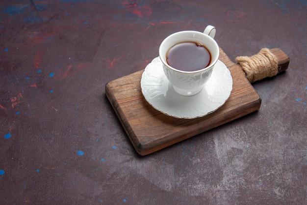 Vista frontal de la taza de té dentro de la taza de vidrio con placa en el espacio oscuro