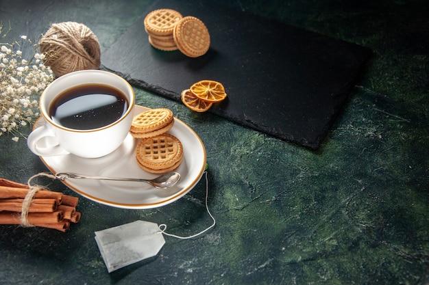 Vista frontal taza de té con galletas dulces en la superficie oscura ceremonia de bebida de pan desayuno dulce foto de la mañana pastel de azúcar colores de vidrio