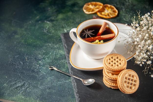Vista frontal de la taza de té con galletas dulces en la superficie oscura ceremonia de bebida de pan de vidrio dulce desayuno pastel foto en color azúcar
