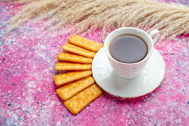 Vista frontal de una taza de té con galletas en el escritorio rosa