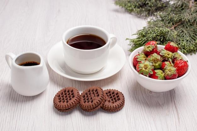 Vista frontal de la taza de té con galletas y fresas en el escritorio blanco azúcar galletas de té galletas dulces