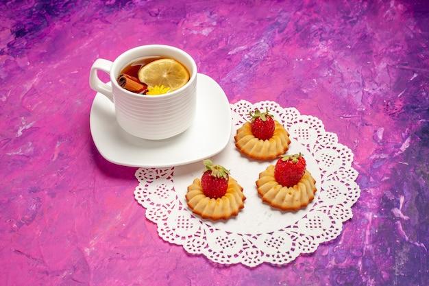 Vista frontal de la taza de té con galletas en la mesa rosa té color caramelo limón