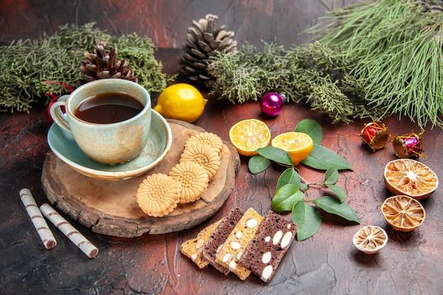 Vista frontal de la taza de té con galletas y pastel sobre fondo oscuro