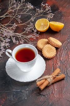 Vista frontal de la taza de té con galletas sobre fondo oscuro
