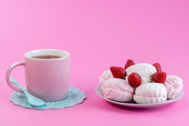 Vista frontal de una taza de té junto con blanco, merengues y fresas frescas dentro de la placa en rosa, dulces de pastel de galletas de té