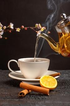 Vista frontal de una taza de té con limón, canela y hervidor de agua en el escritorio gris