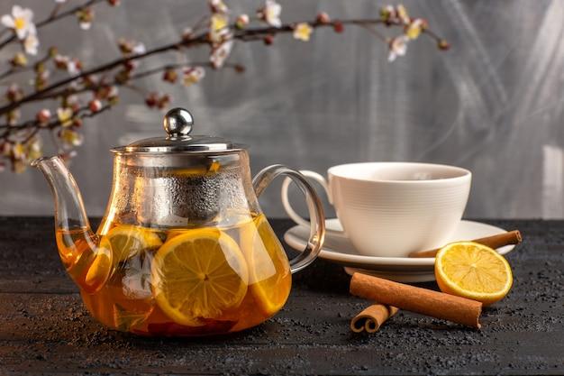 Vista frontal de la taza de té con limón, canela y hervidor sobre superficie gris