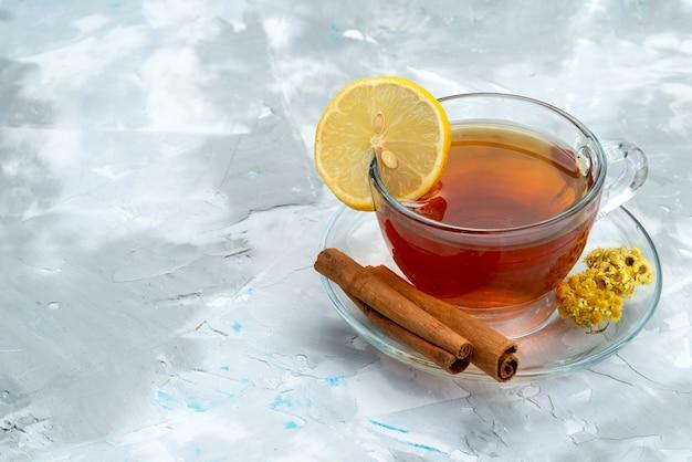 Vista frontal de una taza de té con limón y canela en un postre de frutas brillante, bebida