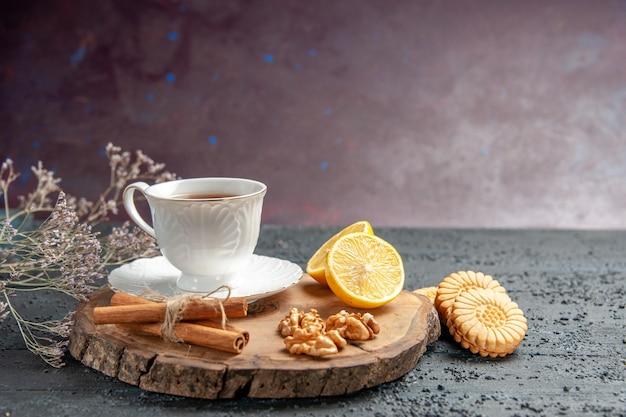 Vista frontal de una taza de té con limón y galletas sobre fondo oscuro