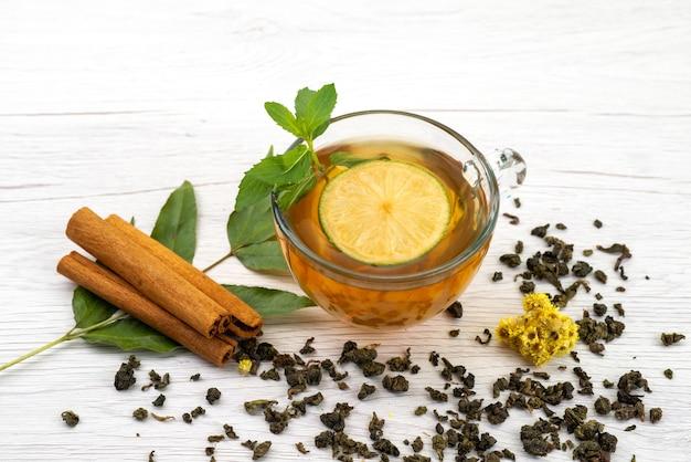 Vista frontal de una taza de té con limón, menta y canela en blanco, dulces de postre de té