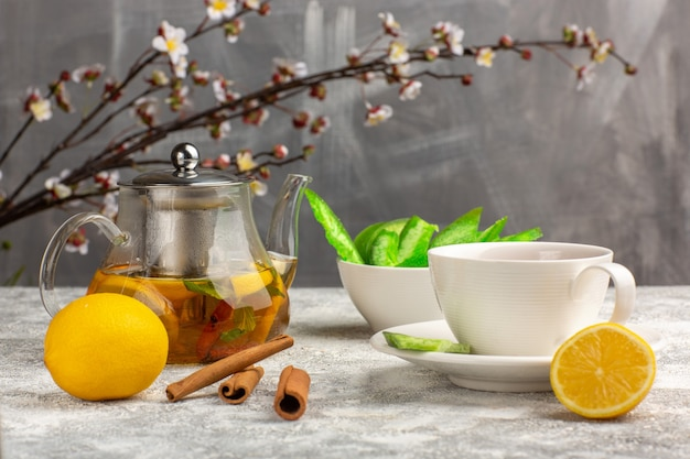 Vista frontal de una taza de té con limones y canela en la superficie de color blanco claro