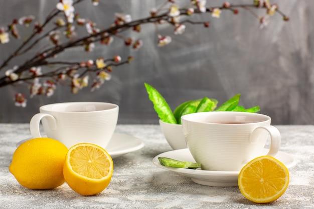 Vista frontal de una taza de té con limones sobre una superficie blanca clara