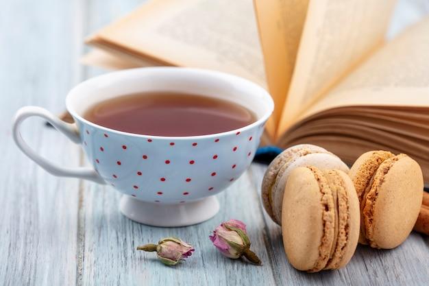 Vista frontal de una taza de té con macarons y un libro abierto sobre una superficie gris