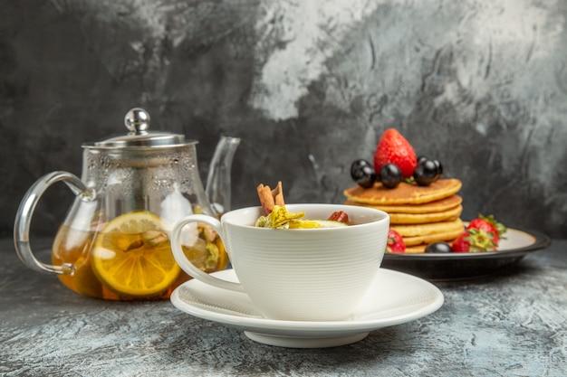 Vista frontal de una taza de té con panqueques y frutas en la superficie oscura, comida de desayuno por la mañana