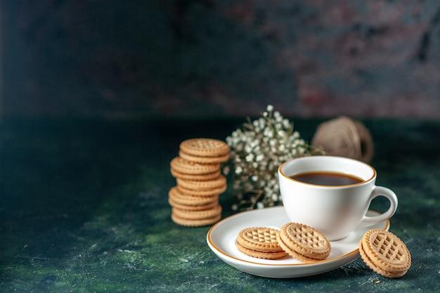 Vista frontal taza de té con pequeñas galletas dulces en un plato blanco sobre fondo oscuro color del pan ceremonia desayuno bebida de la mañana foto de azúcar