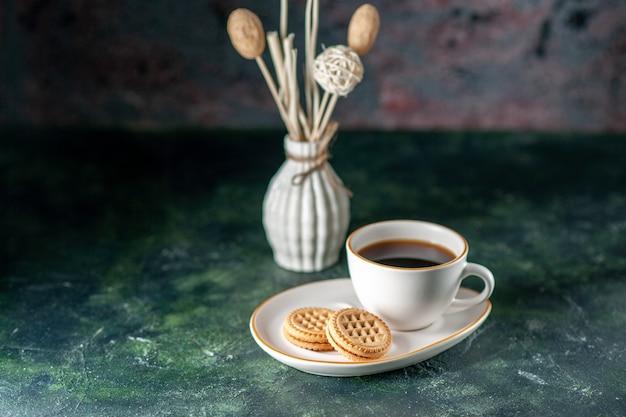 Vista frontal taza de té con pequeñas galletas dulces en un plato blanco sobre la superficie oscura ceremonia de color desayuno foto de la mañana bebida de vidrio