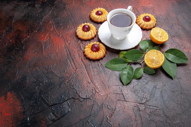 Vista frontal de una taza de té con pequeñas galletas sobre fondo oscuro
