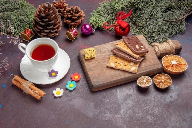 Vista frontal de una taza de té con rebanadas de pastel en el espacio oscuro