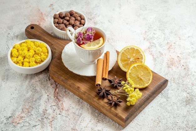 Vista frontal de una taza de té con rodajas de limón y canela en el espacio en blanco