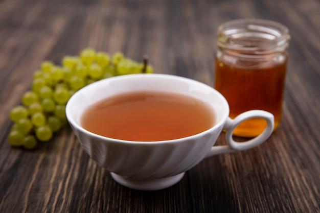 Vista frontal de una taza de té con uvas verdes y miel en un frasco sobre fondo de madera