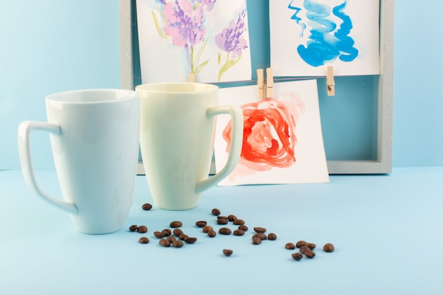 Una vista frontal de tazas blancas con colgantes y semillas de café.