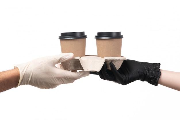 Una vista frontal de tazas de café entregadas de mujer a hombre