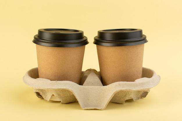 Una vista frontal de tazas de café de plástico entrega café en la mesa amarilla entrega de bebidas de café