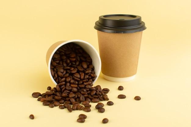 Una vista frontal de tazas de café de plástico con semillas de café marrón sobre la superficie amarilla