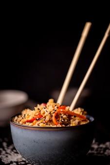 Vista frontal del tazón de comida asiática con palillos