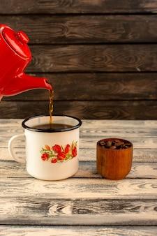Vista frontal del té caliente que vierte de la tetera roja en el escritorio de madera