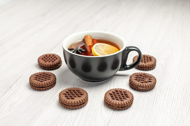 Vista frontal del té de limón y canela redondeado con galletas en el fondo de madera blanca