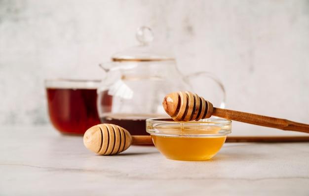 Vista frontal de té y miel sobre fondo blanco.