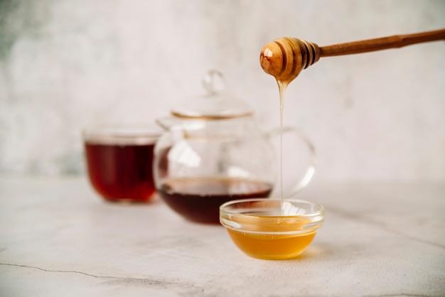 Vista frontal de té y miel sobre fondo borroso