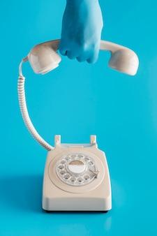 Vista frontal del teléfono antiguo con la mano en el guante sujetando el receptor
