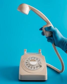 Vista frontal del teléfono con la mano en el guante sujetando el receptor