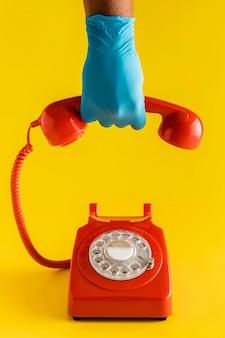 Vista frontal del teléfono retro con la mano en el guante sosteniendo el receptor