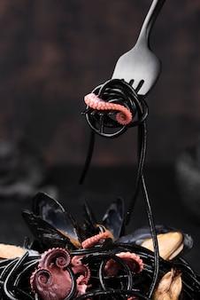 Vista frontal del tenedor con pasta negra y calamares
