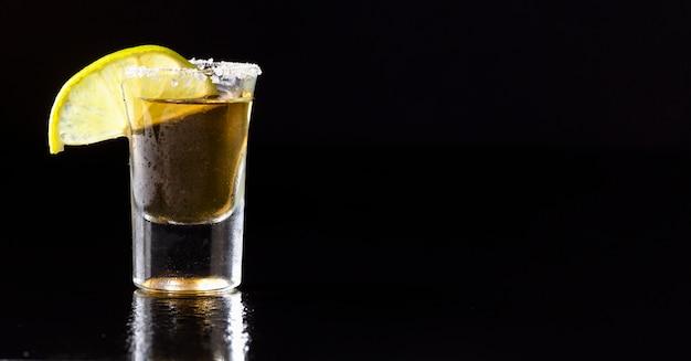 Vista frontal de tequila dorado con limón y espacio de copia