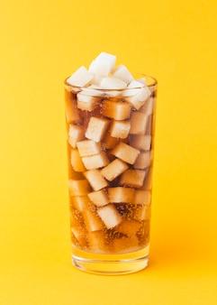 Vista frontal de terrones de azúcar en vidrio con refresco
