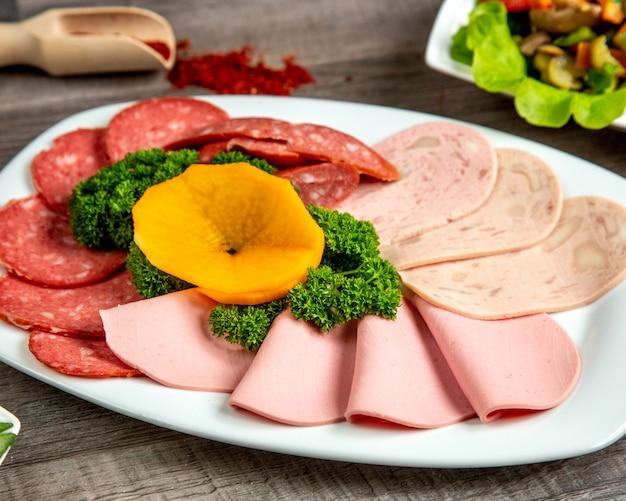 Vista frontal de un tipo de salchicha en un plato con hierbas y especias en la mesa