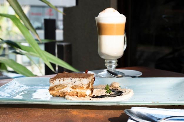 Vista frontal tiramisú con café con leche macchiato