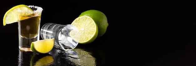Vista frontal de tiro de tequila dorado y lima con espacio de copia